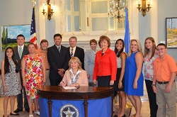 Oklahoma Governor Mary Fallin (seated, center) signs State Senate Bill 262, with the bill's sponsor, Oklahoma State Senator Susan Paddack (fifth from right); Mark Costello, Oklahoma Labor Commissioner (center); Lester Claravall, Oklahoma Dept. of Labor (fifth left); Andrea Okun, NIOSH (center); and Stacy Oakley (third from left), her husband, and her students from Latta Schools in Ada, OK, who worked tirelessly to champion the passage of this first-of-its-kind bill.
