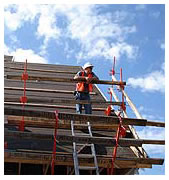 Worker high upon a 45 degree roof leaning on a NIOSH designed roof bracket safety rail system.