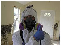 Scientist fully enclosed in protective clothing in a once flooded residence.