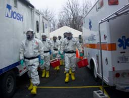 a group of seven emergency responders in protective gear walking toward the viewer between an ambulance on the right and a NIOSH branded trailer on the left.