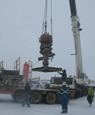 photo of workers outside using a crane with snow on the ground