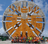 Approximately twenty workers posing in two rows in front of a very large Working Face of a Tunnel Boring Machine (TBM)
