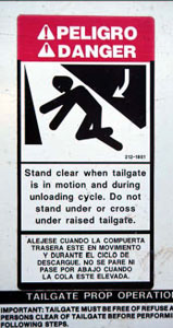 "Photo 2. Warning sign: ""Stand  clear when tailgate is in motion and during unloading cycle."""