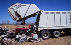 Photo 4. The compactor in the upright position, emptying its contents onto the ground.
