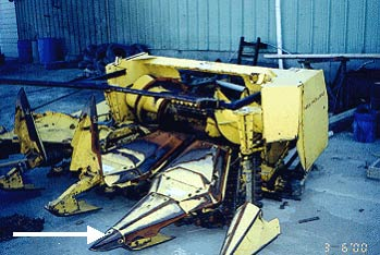 corn chopper head  disconnected from forage harvester, the arrow points to one of the tongs