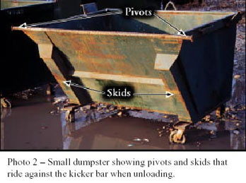 Photo 2 - Small dumpster showing pivots and skids that ride against the kicker bar when unloading.