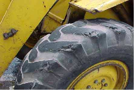 Photo 9.  Left front-drive tire.  Note missing tread and chunks of rubber.