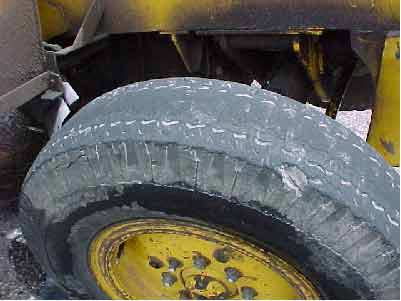 Photo 12.  Left rear-steer whieel.  Note the large chunk of rubber and most tread missing.