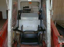 Figure 2. View of cab with seatbelts and restraint bar.