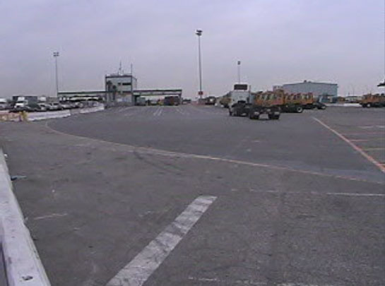 Exhibit 4. A picture of the incident scene looking east. The forklift parking area is on the right of the picture. The employee parking lot is on the left of the picture. The top handler was headed to the area on the left of the picture.