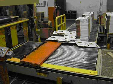 Exhibit #2. A picture of the automated roller conveyor system that brings the boxes to the table that feeds the boxes into the waxing system.