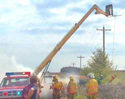 Photo 1 - View of firefighters at the scene, showing the forklift near the powerlines and the pump suspended by a wire rope cable.