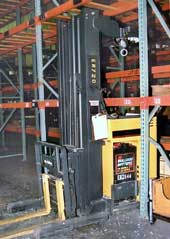 Photo 1 - Left-front view of the forklift, positioned as it was found under the empty metal rack beam.
