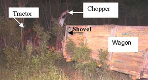 Figure 2. Tractor, chopper, trailer wagon stalled in tree line next to field.
