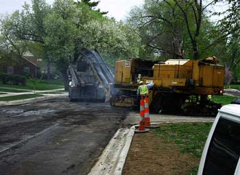 Milling machine discharging asphalt residue into waiting dump truck.
