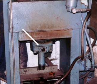 The lower front part of the shop-fabricated hydraulic press involved in this incident shows a hole where a hose was attached to the hydraulic cylinder.
