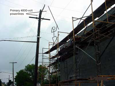 drawn in stickman on scaffold with rod touching powerlines