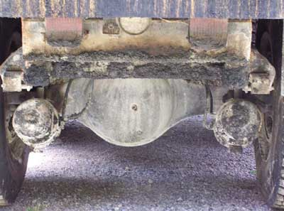 Photo 3: Picture of brakes and pneumatic lines at rear of truck. Truck bed is flat.