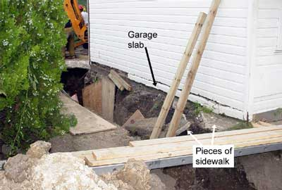 arrows point to the garage slab and pieces of sidewalk in the collapsed trench.