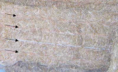 Nylon strings indicated by arrows around the hay bale