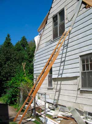 Figure 1. Siding being removed, ladder propped against fence.