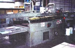 The glue press operates on an automatic cycle, with a conveyor running beneath a glue roller and into the press.