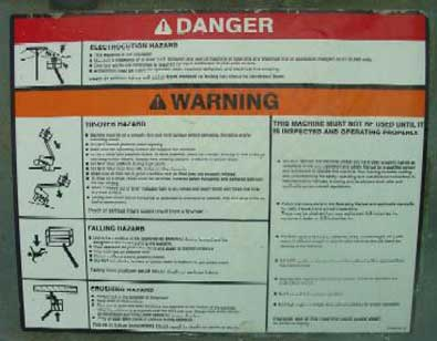 The warning label on the aerial platform illustrates the hazards of electrocution, falling, or striking an overhead obstacle.