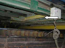 A traveling bar under the stacker moves an alignment chain. Arrow shows bar and direction of travel.