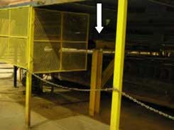 Arrow shows the horizontal crossbeam under the stacker, inside the barricaded area.