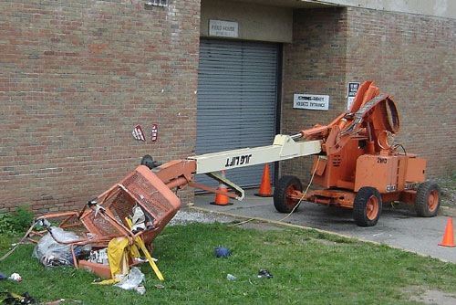 Photo 2. The aerial work platform collapsed during the incident and the lift basket crashed to the ground and landed on the grassy surface by the Field House.