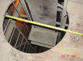 The victim fell through this manlift shaft opening. A platform step is shown on the lift belt, and the fixed ladder and stop cord at left.