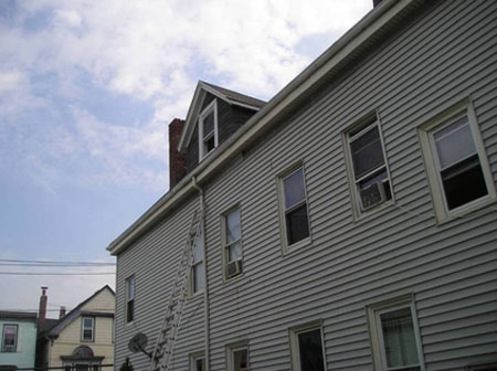 Neighboring house where the incident took place. Note the loose piece of vinyl siding to the right and above the top of the ladder.