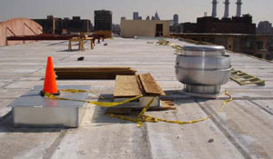 Figure 1. Make-up air roof curb with orange pylon, exhaust fan roof curb with plywood, looking south on roof.