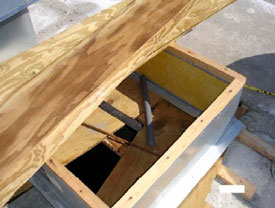 Figure 4. Chase A exhaust fan hole with 2x4 lumber and plywood boards as cover.