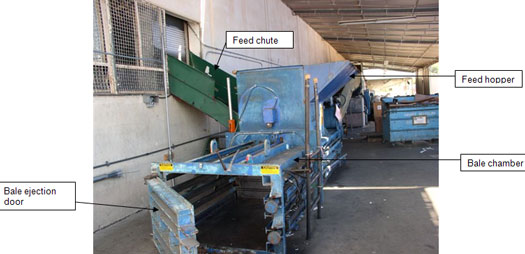 The cardboard baler showing the feed chute and chamber where the recycled bales of cardboard were formed.