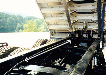 photo shows pull-off      cable running along the truck's frame to rear of dump bed