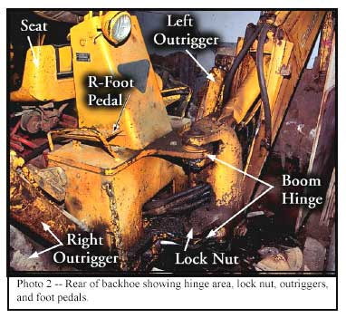 Photo 2 -- Rear of backhoe showing hinge area, lock nut, outriggers, and foot pedals