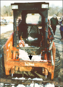 arrow points to cross member of boom lift-arm assembly of skid steer loader