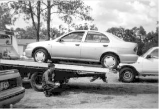 file photo of a flatbed unloading a car