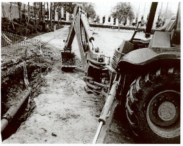 photo shows image of bucket and boom of backhoe