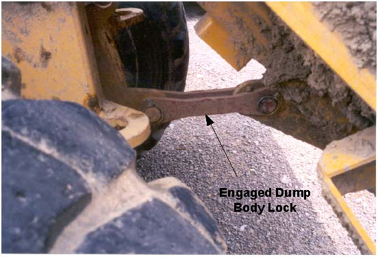 Dump body lock when dump body is in the raised position and the dump body lock has been engaged.