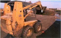 Skid steer loader. Shows approximate location on horizontal bar of scraper attachment which came down and crushed the victim's head.