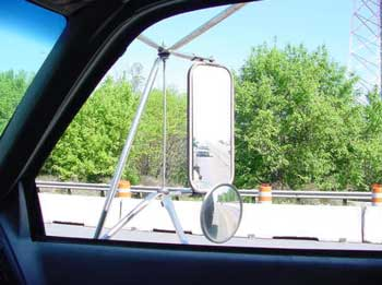 Mirrors mounted on each door of the dump truck.