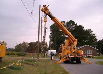 A boom truck with an auger attached was turning a utility pole anchor in an anchor-setting process.