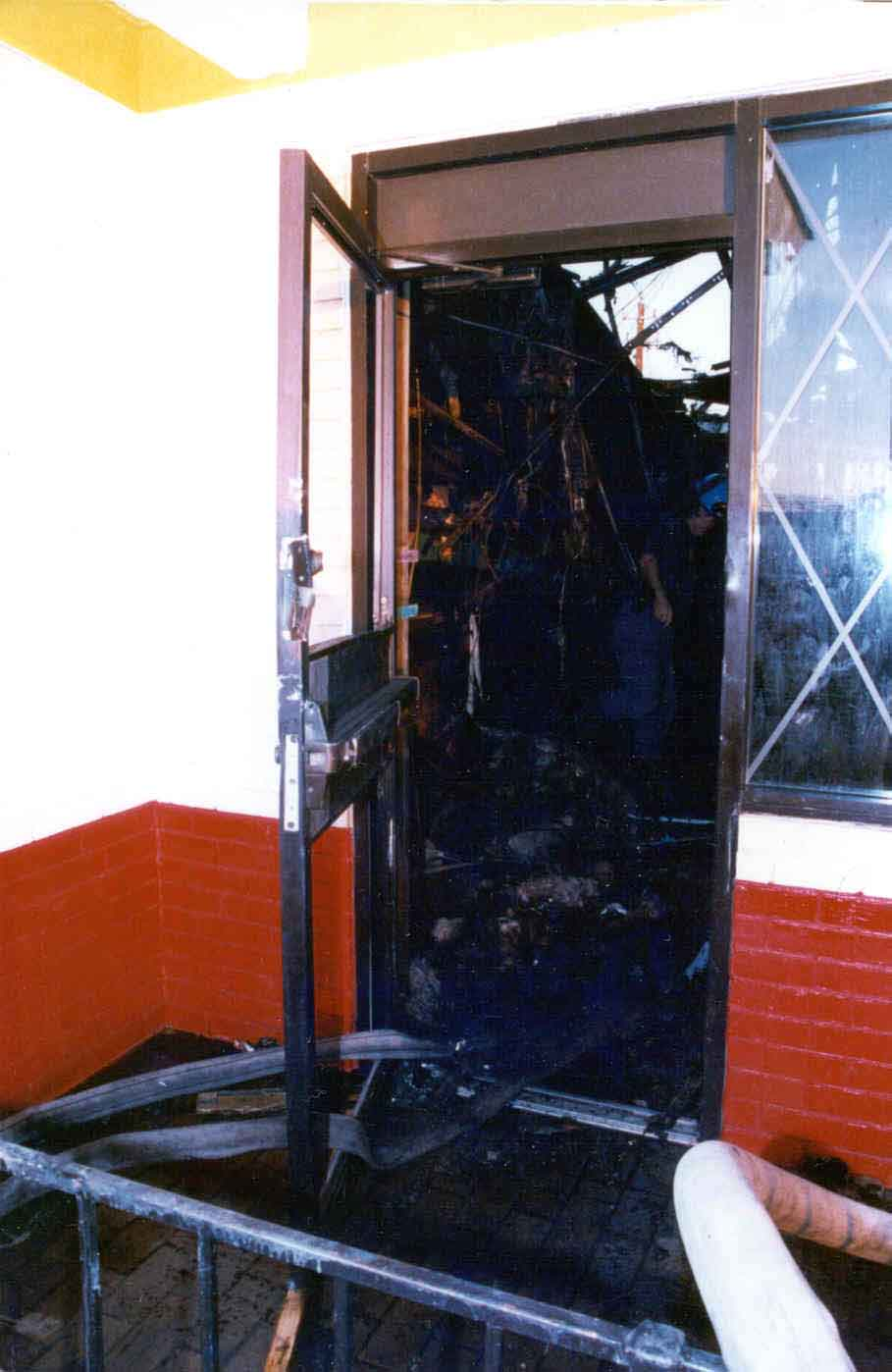 Photo 6: Post-fire, exterior view of the west side door of the restaurant.
