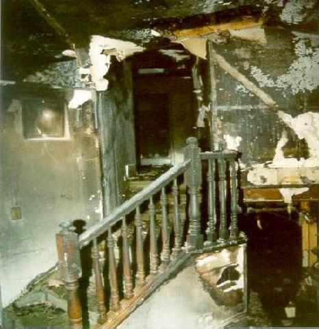 Front page photo: Interior photo of the burned-out stairwell of the house.