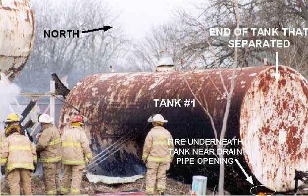Photo 1: Photograph of Tank #1 prior to explosion, showing the approximate location of the fire under the tank and the end of the tank that exploded.