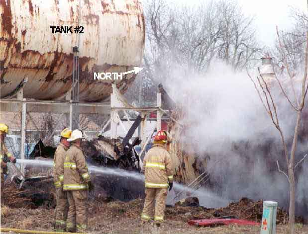 Photo 2: Photograph of the south side of Tank #1 prior to the explosion, showing fire fighters applying water to the tank's surface.