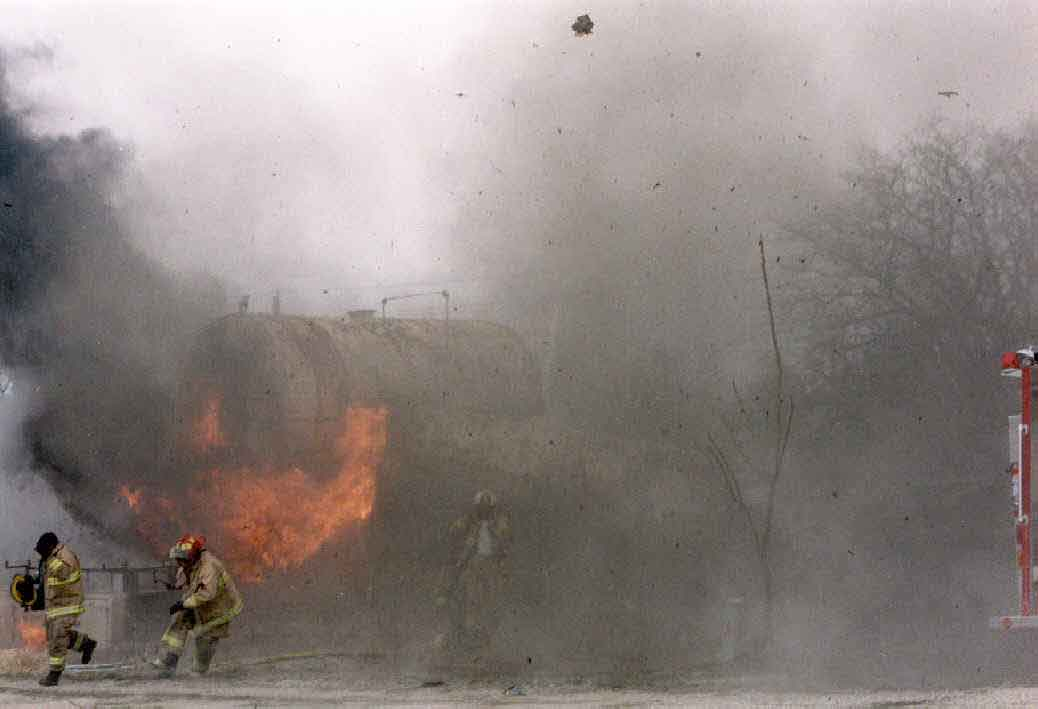 Photo 3: Photograph of Tank #1 burning immediately after the explosion, showing fleeing fire fighters.