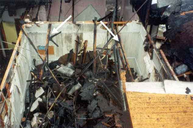 Photograph of burned-out structure, showing truss and gusset plates.